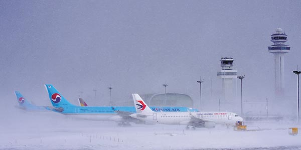 Planes stranded on the runway of Jeju International Airport on Sunday after flights were suspended Saturday afternoon due to heavy snow. [HALLA ILBO]