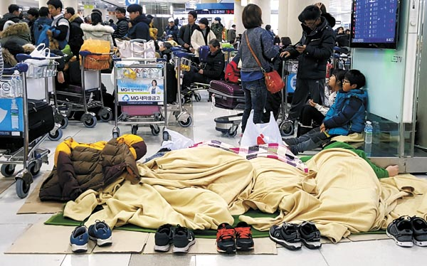 Passengers camp on the floors of the Jeju International Airport early Sunday, waiting for airlines to resume flights out. A flight ban was extended to early Monday after the weather conditions got worse. [NEWSIS]