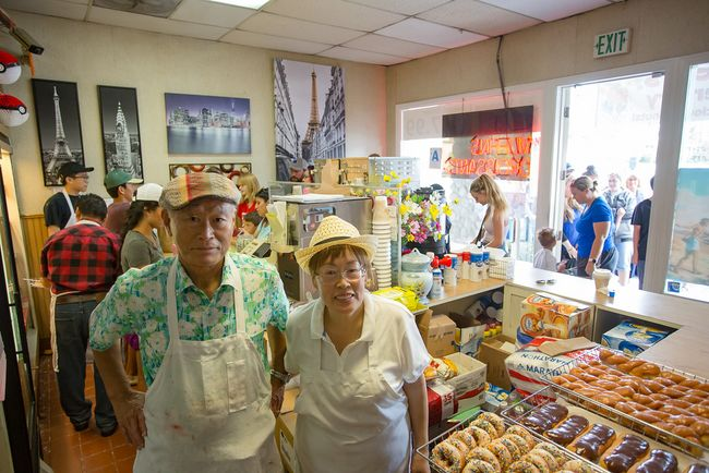 Sesame Donuts owners Jin-woong Kim and Jennifer Kim as they take customers on the day of their 27-year anniversary. (photo provided by Erika Thornes)