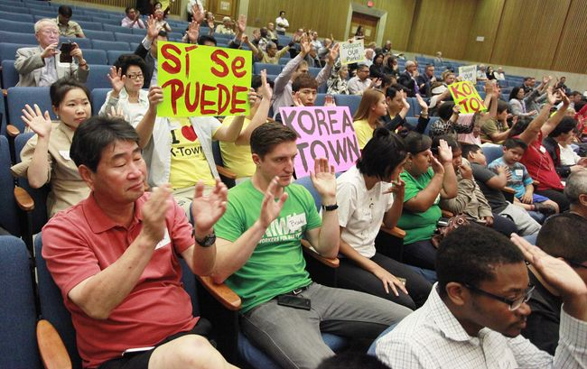 Koreatown residents holding a sign in support of building a community center on Vermont Avenue between 4th and 6th Streets at the L.A. County Board of Supervisor meeting on Tuesday. Sang Jin Kim