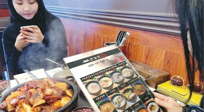 Many Koreatown businesses are making an effort to understand the consuming habits of their Chinese customers. The photo is showing customers looking through a Chinese-language menu at a Korean restaurant.