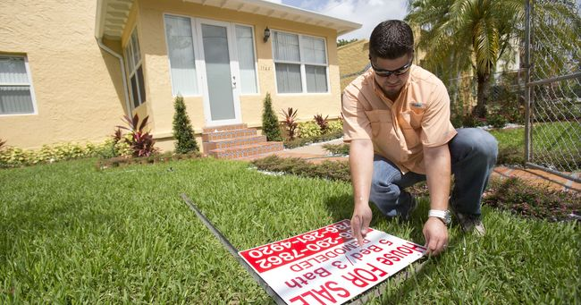 Buyers are gaining bigger leverage in the home-buying market as sellers are lowering their asking price. A homeowner is changing his listing price. [AP]