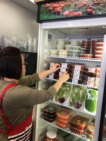 Meat shops in Koreatown are seeking better sales by increasing the number of non-meat items at their businesses. Shin Sun Meat owner Keum-sook Joo is organizing the side dish items at her shop.