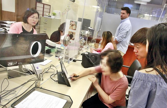 L.A.'s South Korean consulate office has received 146 applicants for the new consulate ID card, which was first released on Oct. 4, marking a daily average of 30. An applicant is submitting a request for the new ID card over the counter at the consulate office on Oct. 12. Sang Jim Kim