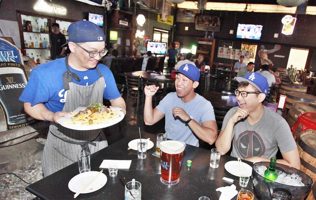 Dodger fans rooting for their team during the National League Championship Series Game 4 at Koreatown bar Mokmarjong on Wednesday. Sang Jin Kim