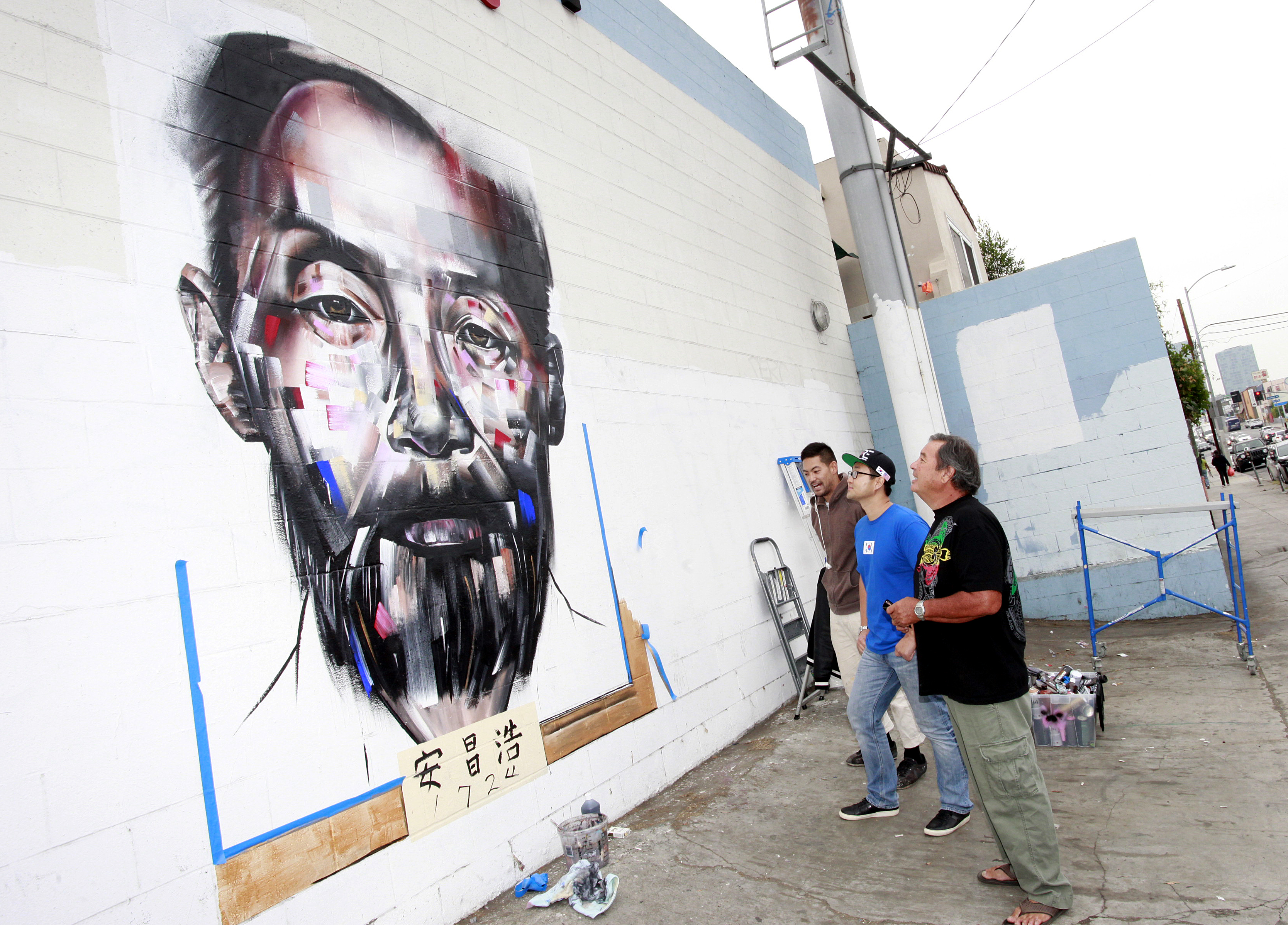Mural artist Joseph Lee, KORE CEO Matthew Kim, and Ahn Chang-ho's grandson Phillip Ahn Cuddy, are staring at the portrait of Dosan