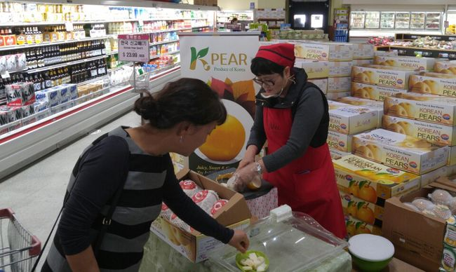 A customer at Galleria Market in Northridge is tasting a pear.