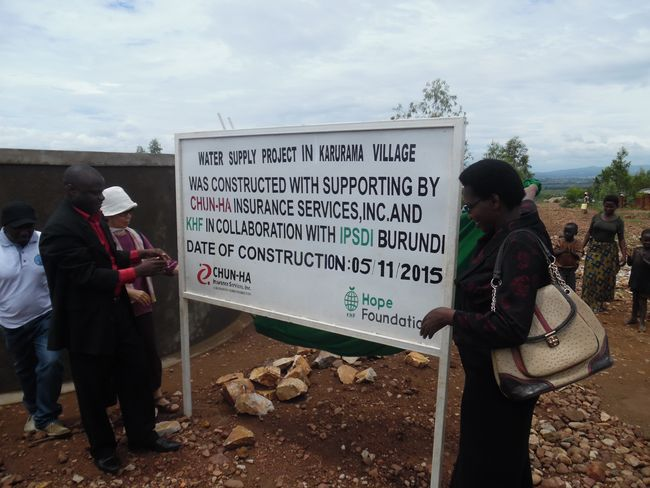Public servants and local residents in Karurama, Burundi is putting up a sign to notify construction of the water supply system in May of last year. Chun-Ha Insurance Services has been helping them annually through a paid raffle contest.